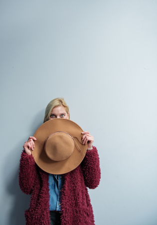 Joyful young woman is hiding face behind big hat. She is looking at camera with excitement while standing near wall. Copy space above