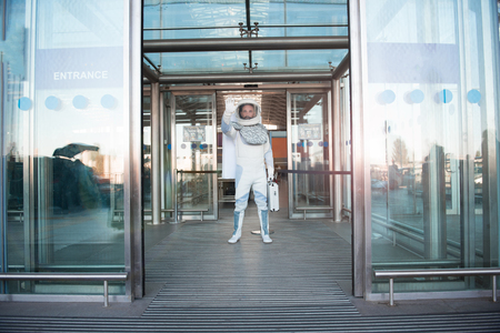 Hope it is not dangerous. Confident astronaut ready for going out and looking ahead with seriousness. Full length portrait. Copy space on right side