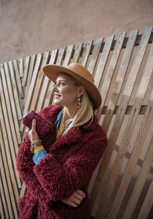 Profile of gorgeous young lady leaning on wooden fence and relaxing. She is holding small purse and laughing