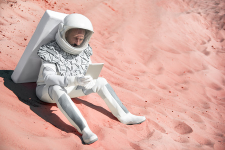 Thoughtful spaceman wearing white armor is sitting on red sand and holding tablet. Copy space on right side