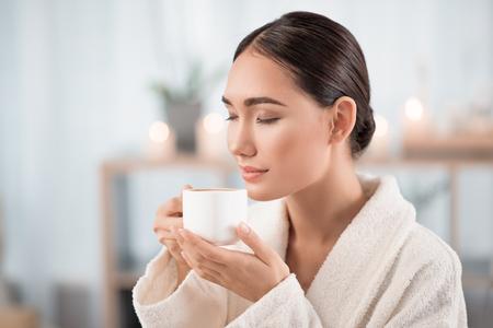 素晴らしい香り。ゴージャスな若いアジア女性は目を閉じて新鮮なエスプレッソの臭いがする、満足度を表現します。彼女は美容院で白いバスロー