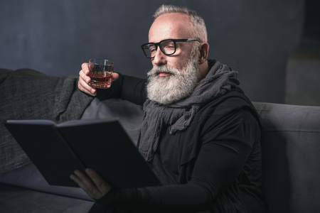 Portrait of glad bearded retire man relaxing on sofa while tasting delicious alcohol liquid in apartment. He reading book. Leisure concept