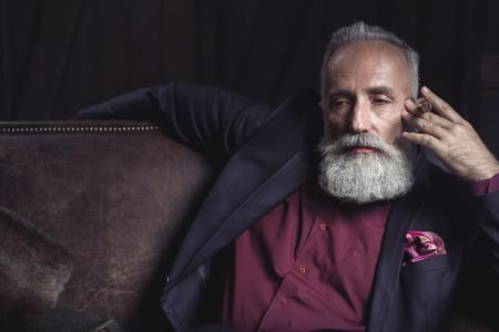 Portrait of pensive unshaven retire tasting cigarette while sitting on cozy sofa. Dreaminess concept