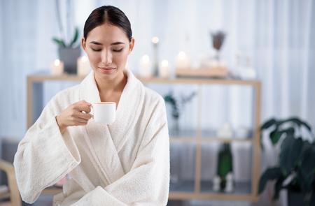 コーヒー タイム。リラックスしたアジアの女の子のウエスト アップ肖像画は、ウェルネス センターで時間を過ごしながらテリー バスローブを着て 写真素材