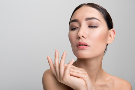 Skincare. Portrait of elegant naked dark-haired asian woman touching her palm with tenderness while being delighted with her skin and looking down dreamily. Isolated with copy space