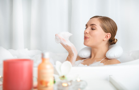 Carefree young woman is blowing on foam in her hand while lying in bath with pleasure Stock Photo