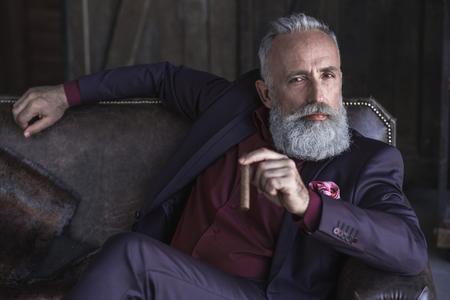 居心地の良いソファーで休んでいる間穏やかなひげを剃っていない成熟した男性喫煙葉巻の肖像画。高級コンセプト