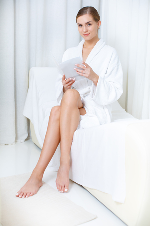 Full length portrait of happy young girl resting after skincare treatment in wellness center. She is holding magazine while sitting on deckchair in relaxation room. Lady is smiling