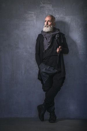 Full length portrait of calm bearded pensioner keeping beads while standing in apartment. Style concept. Copy space