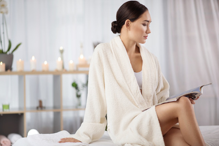Comfortable atmosphere. Profile of young attractive asian girl in terry bathrobe is sitting on couch in cozy wellness center while reading magazine thoughtfully. Copy space in the left side