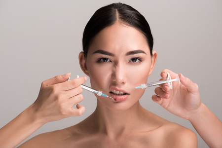 Beauty requires sacrifice. Portrait of naked young asian woman is having facial collagen injection by syringe. She is standing and looking at camera while feeling pain. Isolated background
