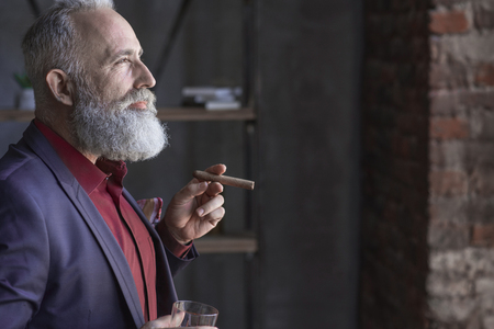 Side view glad bearded old man tasting cognac and holding tobacco while locating in apartment. Rest concept. Copy space Stock Photo