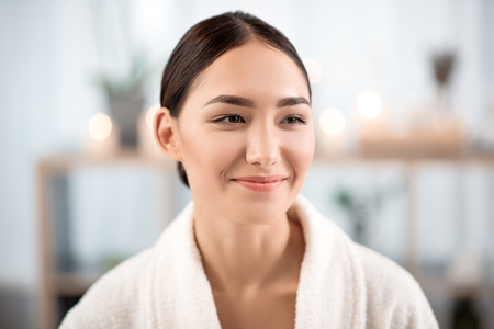 Happy mood. Portrait of cheerful mysterious young asian girl in terry bathrobe is spending time in beauty salon. She is looking aside with smile while resting with pleasure