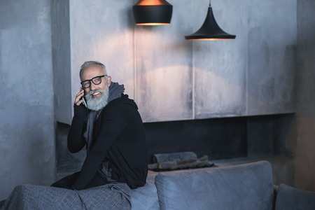 Portrait of cheerful unshaven retire male speaking by phone while sitting on sofa in living room. Equipment concept