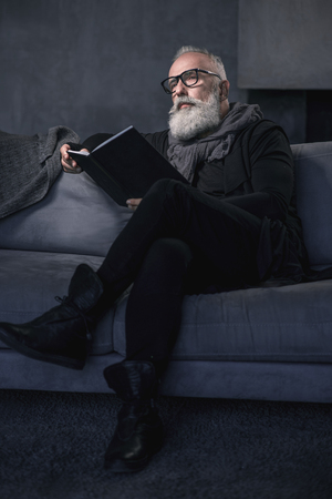 Full length low angle portrait of serene mature man looking through volume while sitting on comfortable couch in living room. Relax concept