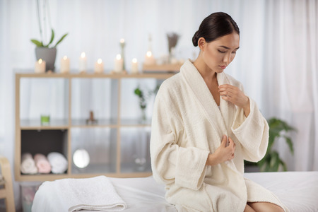 Pleasant weekends. Attractive relaxed asian girl is sitting on massage table at wellness center with candles in background. She is taking off her white bathrobe. Copy space in the left side