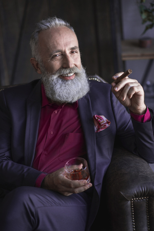 Portrait of beaming bearded senior tasting delicious beverage while holding tobacco in arm. Relax concept