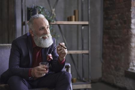 Il ritratto della risata barbuta si ritira assaggiando l'alcool e tenendo in mano il tabacco. Concetto di piacere. Copia spazio Archivio Fotografico - 90592630