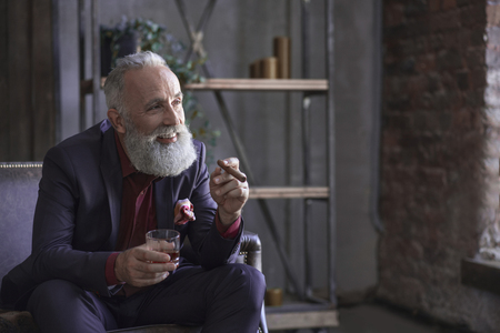 Portrait of laughing bearded retire tasting alcohol and holding tobacco in hand. Pleasure concept. Copy space 免版税图像 - 90592630