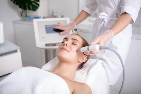 Opinião lateral a jovem mulher feliz que obtém a cavitação que rejuvenesce o tratamento da pele em termas. Ela está deitada na mesa de massagem e sorrindo. Esteticista está tocando a tela do monitor, mantendo a ferramenta perto da bochecha feminina