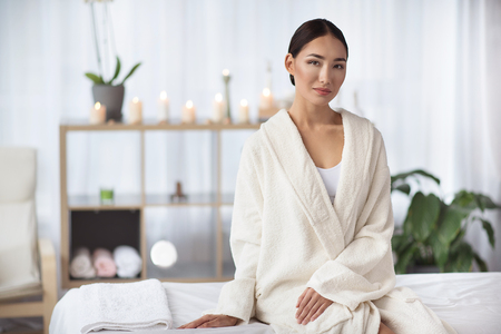 Have rest. Portrait of elegant relaxed young asian woman in white bathrobe is sitting on massage table at spa salon with candles in background. She is looking at camera thoughtfully. Copy space Stock Photo
