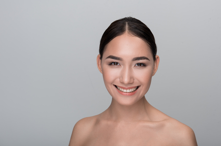Daily skincare. Portrait of optimistic young naked asian girl with fresh and clean face. She is looking at camera with wide smile. Isolated background and copy space in the left side