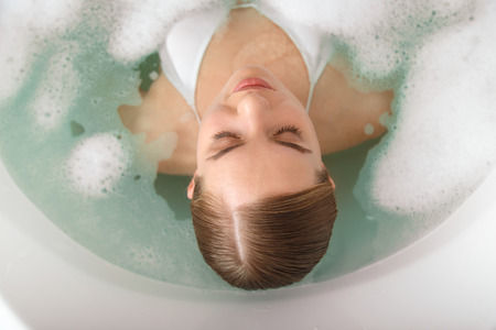 泡とお湯を楽しんでリラックスした若い女性の平面図です。彼女は、喜びとバスタブに横たわっています。