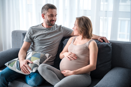 I will take care of you both. Affectionate man is looking at pregnant woman with love and smiling. They are sitting on couch in living room