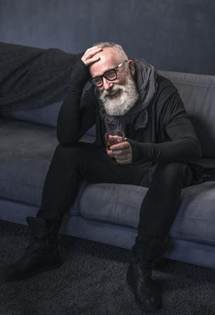 Full length portrait of beaming bearded pensioner tasting delicious beverage while situating on comfortable couch in room. Rest concept