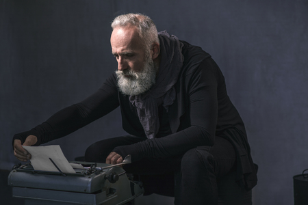 Side view serene unshaven old man typing new novel in printing machine while sitting in apartment. Inspiration concept Stock Photo