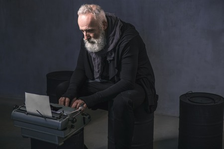 Side view serious unshaven old author typing in printing machine while sitting on black barrel. Inspiration concept. Copy space Stock fotó
