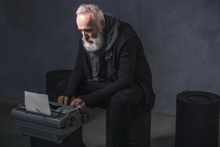 Zijaanzicht het ernstige ongeschoren oude auteur typen in drukmachine terwijl het zitten op zwart vat. Inspiratie concept. Kopieer ruimte