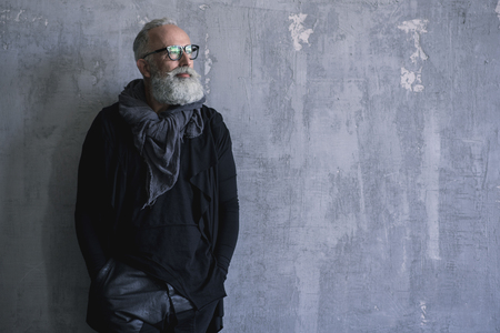 Portrait of pensive unshaven grandfather leaning against wall. Copy space. Fashion concept
