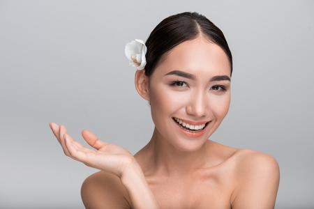 Koncepce krásy. Portrét hravé mladé nádherné asijské dívky s bílou orchidejí ve vlasech. Dívá se na fotoaparát s radostí, zatímco gestikuluje pozitivně. Izolované pozadí