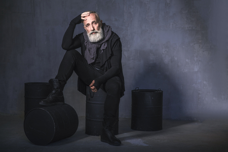 Full length portrait of pensive unshaven retire holding accessory in hand while sitting on black barrels in room. Thought concept. Copy space