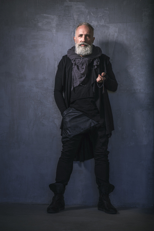 Full length portrait of serene trend-perfect unshaven senior holding accessory while locating in room. Fashion concept