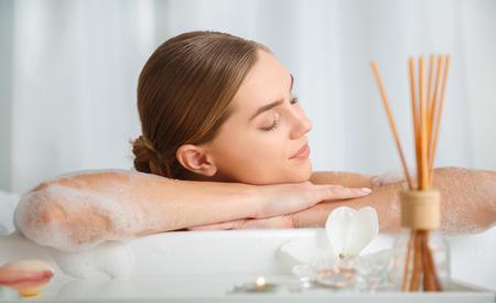 平和と快適さ。浴槽で眠っている穏やかな女の子。彼女はリラクゼーションの腕に頭を傾いています。 写真素材