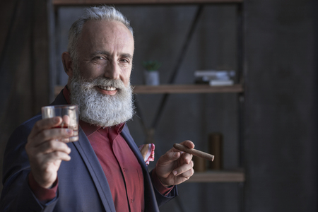 Cheer. Portrait of smiling elegant bearded old businessman tasting appetizing alcohol and keeping tobacco. Celebration concept