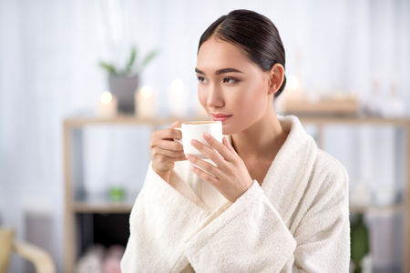 Fresh espresso. Gorgeous asian girl is drinking hot coffee while resting in spa salon. She is sitting in white terry bathrobe while looking aside with slight smile. Shelves with candles in background Banco de Imagens