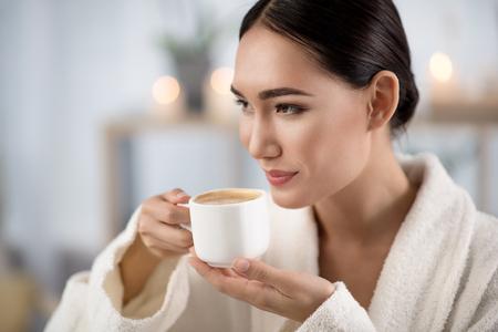 私の好みの飲料。魅力的な楽観的なアジアの女の子は、ウェルネス センターでリラックスしながら新鮮なコーヒーを飲んでいます。彼女は笑顔で脇