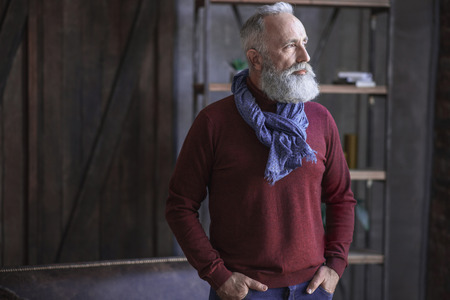 Side view calm bearded old man standing in modern apartment. Reverie concept
