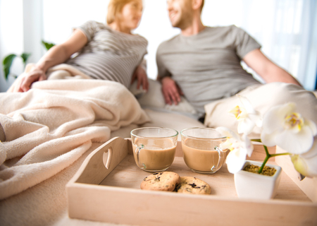 Enjoying pregnancy period together. Close up focus of two cups of coffee, flower and cookie on tray. Glad loving couple is lying on bed and smiling on background