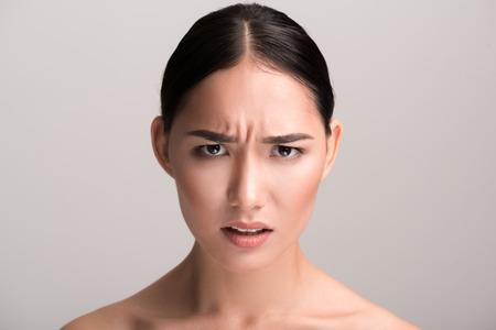 Lleno de ira El retrato del primer de la mujer asiática enojada joven está mirando la cámara con molestia mientras que frunce el ceño su frente. Fondo aislado