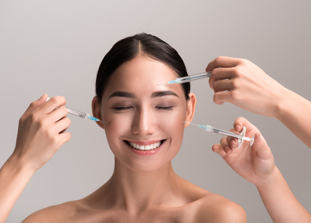 Enjoying care of my skin. Portrait of happy young woman is standing with closed eyes and smiling while hands with syringes are injecting filler or botox into her face. Isolated background Stockfoto