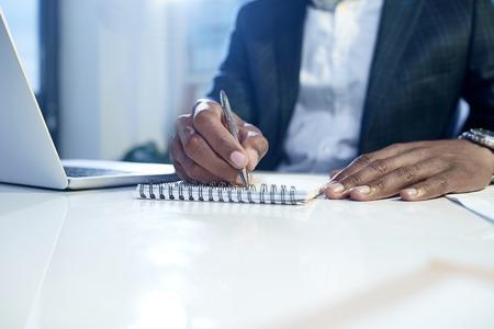 Belangrijke taak. Close-up van handen van gekwalificeerde Afrikaanse zakenman in pak die aan bureau met laptop zit en in zijn voorbeeldenboek schrijft. Selectieve aandacht. Kopieer ruimte