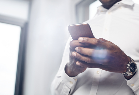 Useful device. Close-up of hands with modern mobile phone. Skillful african businessman in white shirt is holding gadget while standing in light office. Copy space in the left side