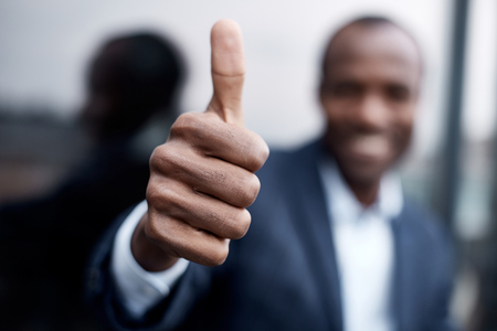 Its OK. Close-up of african businessman hand is showing thumb up while expressing gladness. He is standing outdoors. Focus on hand