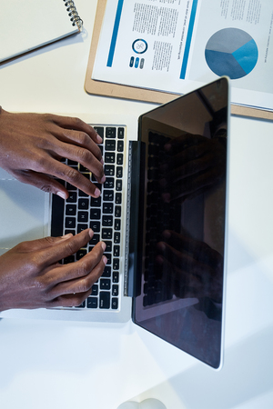 Working space. Close-up top view of african male hands are typing on modern laptop. Man is sitting at desk and working on important project