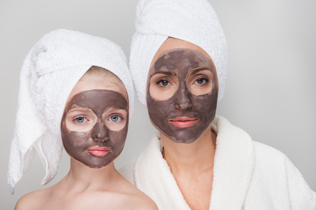 Portrait of pleasant middle-aged mother in bathrobe and her little daughter are standing together with towels on head and facial clay mask while enjoying spa procedures. Isolated. Beauty concept Stok Fotoğraf