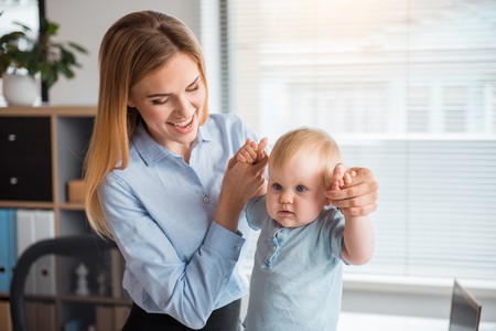 Portrait of beaming young mother holding serene baby in apartment office. Job and infant concept